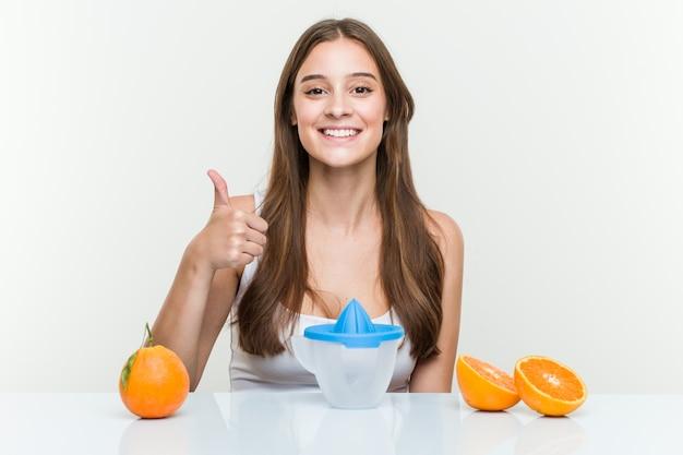 Giovane donna caucasica con uno spremiagrumi arancione che sorride e che alza pollice in su