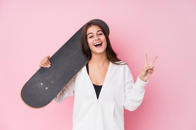 Giovane donna caucasica del pattinatore che tiene il pattino gioiosa e spensierata che mostra un simbolo di pace con le dita.