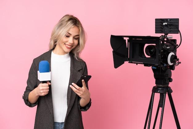 Giovane donna caucasica del reporter sopra la parete rosa isolata