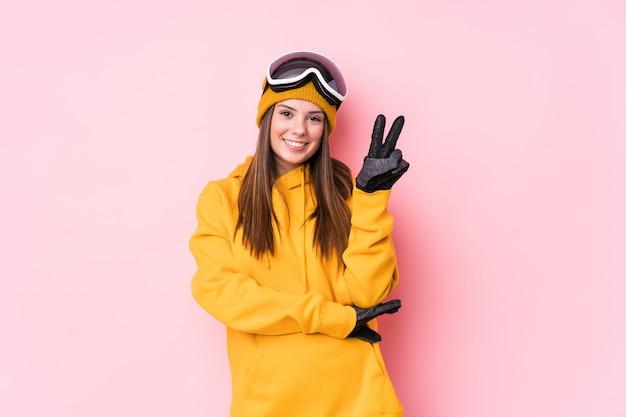 Giovane donna caucasica dello sciatore che mostra numero due con le dita.