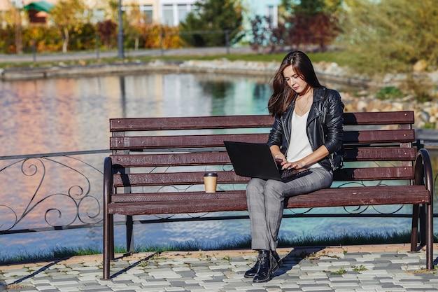 Giovane donna caucasica di affari che si siede alla panchina nel parco e lavora con il computer portatile