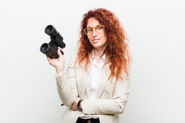 Giovane donna caucasica di affari di redhead che giudica un binocolo felice, sorridente e allegro.
