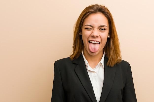 Giovane donna caucasica di affari divertente e amichevole che attacca fuori la sua lingua.
