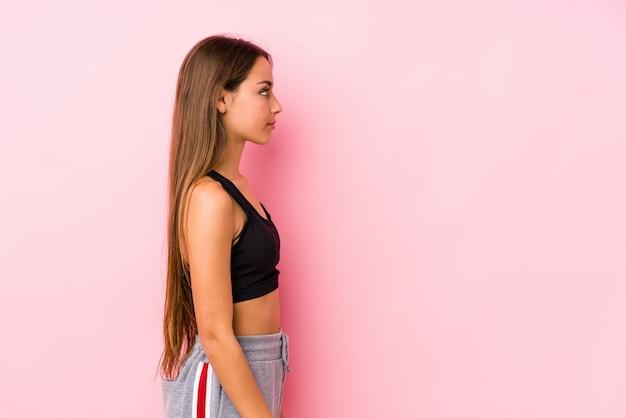 Giovane donna caucasica di forma fisica che posa in una parete rosa che guarda a sinistra, posa laterale.