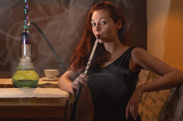 Giovane donna caucasica fuma un narghilè o narghilè nel night club o bar fuma.