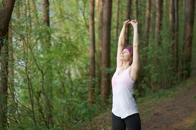 Giovane donna caucasica in attrezzatura sportiva che colpisce prima del pareggiare nella foresta