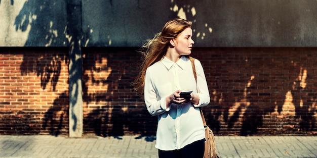 Giovane donna caucasica in piedi utilizzando il telefono cellulare all'aperto