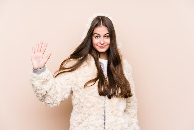 Giovane donna caucasica in posa isolato sorridente allegro che mostra il numero cinque con le dita.