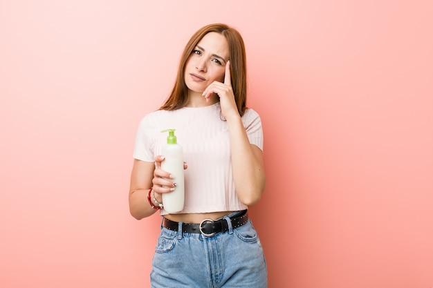 Giovane donna caucasica in possesso di una bottiglia di crema che punta il suo tempio con il dito, pensando, incentrato su un compito.