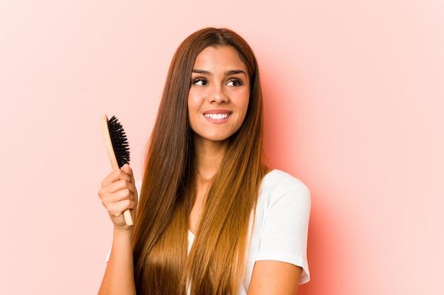 Giovane donna caucasica in possesso di una spazzola per capelli sorridente fiducioso con le braccia incrociate.
