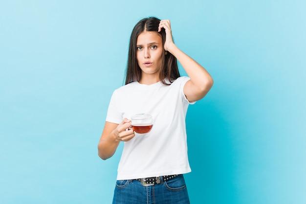 Giovane donna caucasica in possesso di una tazza di tè scioccata, ha ricordato un incontro importante.