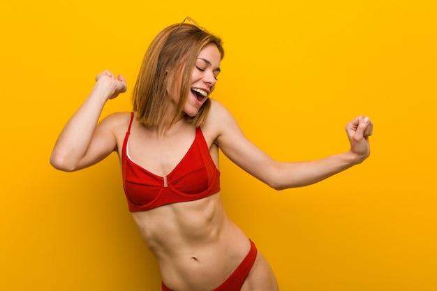 Giovane donna caucasica indossando bikini e occhiali da sole ballare e divertirsi.
