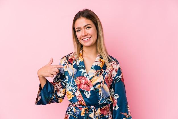 Giovane donna caucasica indossando pigiami persona che punta a mano uno spazio di copia della camicia, orgoglioso e fiducioso