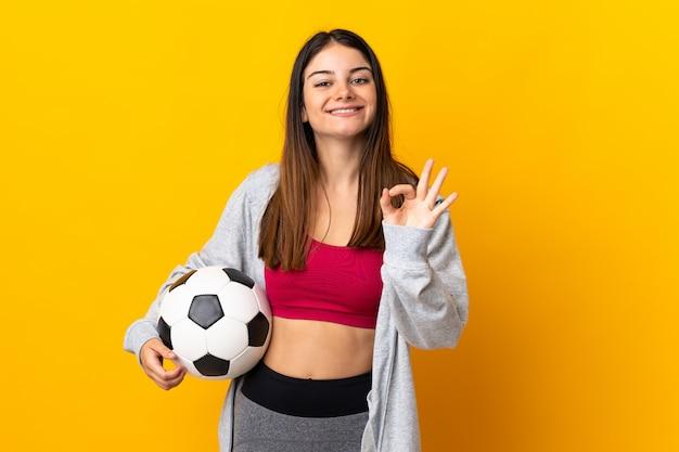 Giovane donna caucasica isolata su giallo con pallone da calcio e facendo segno ok