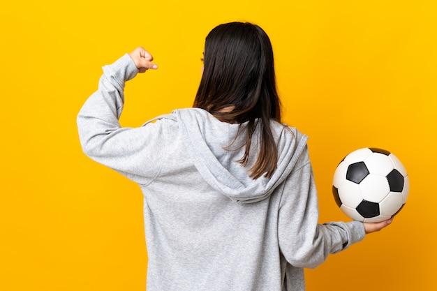 Giovane donna caucasica isolata su giallo con pallone da calcio