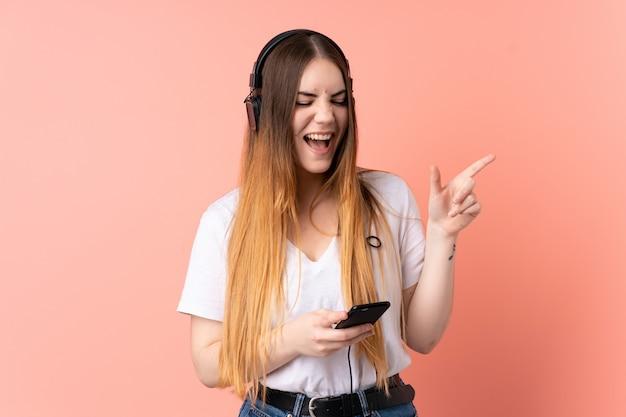 Giovane donna caucasica isolata su musica d'ascolto della parete rosa con un cellulare e cantare