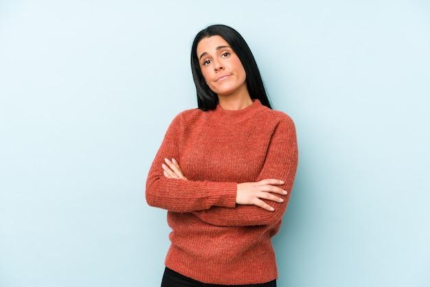 Giovane donna caucasica isolata su una parete blu insoddisfatta dell'espressione sarcastica.