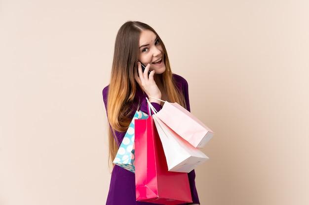 Giovane donna caucasica isolata sui sacchetti della spesa beige della tenuta della parete e chiamare un amico con il suo telefono cellulare