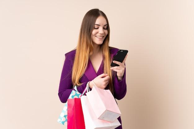 Giovane donna caucasica isolata sui sacchetti della spesa beige della tenuta della parete e scrivere un messaggio con il suo telefono cellulare ad un amico