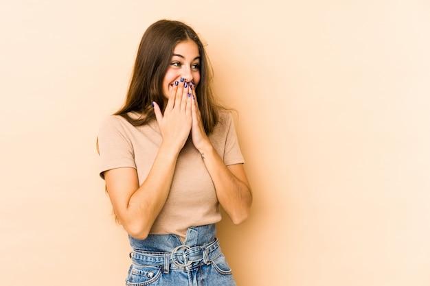 Giovane donna caucasica isolata sul beige che ride di qualcosa, coprendo la bocca di mani.