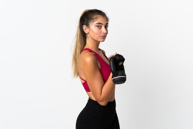 Giovane donna caucasica isolata sul sollevamento pesi di fabbricazione bianco con kettlebell
