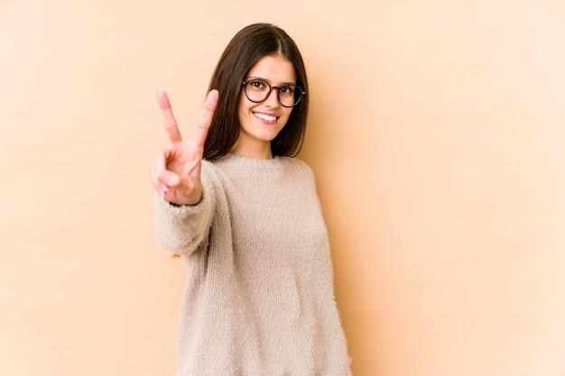 Giovane donna caucasica isolata sulla parete beige allegra e spensierata che mostra un simbolo di pace con le dita.