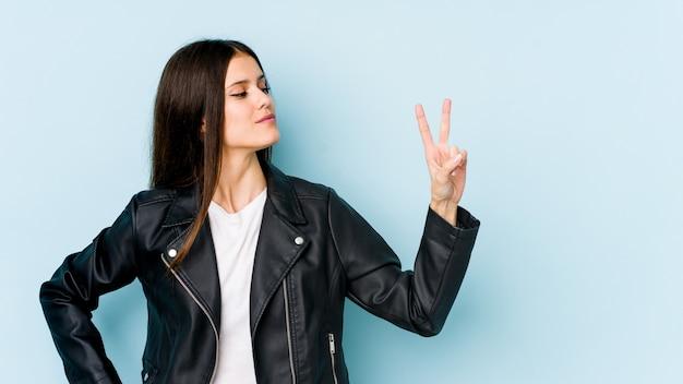 Giovane donna caucasica isolata sulla parete blu allegra e spensierata che mostra un simbolo di pace con le dita.