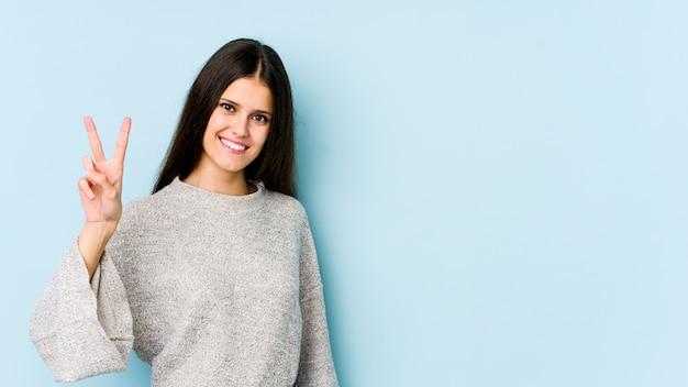 Giovane donna caucasica isolata sulla parete blu che mostra il segno di vittoria e che sorride ampiamente.