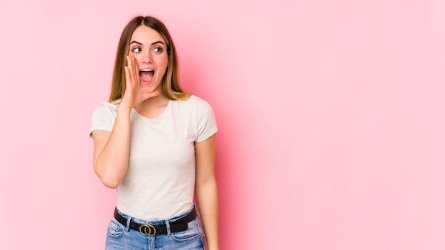 Giovane donna caucasica isolata sulla parete rosa che grida eccitato alla parte anteriore.