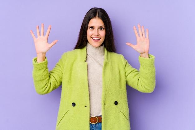 Giovane donna caucasica isolata sulla parete viola che riceve una piacevole sorpresa, eccitata e alzando le mani.