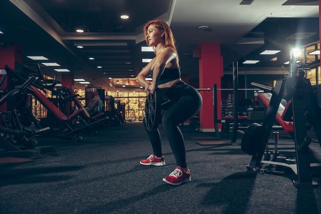 Giovane donna caucasica muscolare che pratica in palestra con attrezzature. benessere, stile di vita sano, bodybuilding.