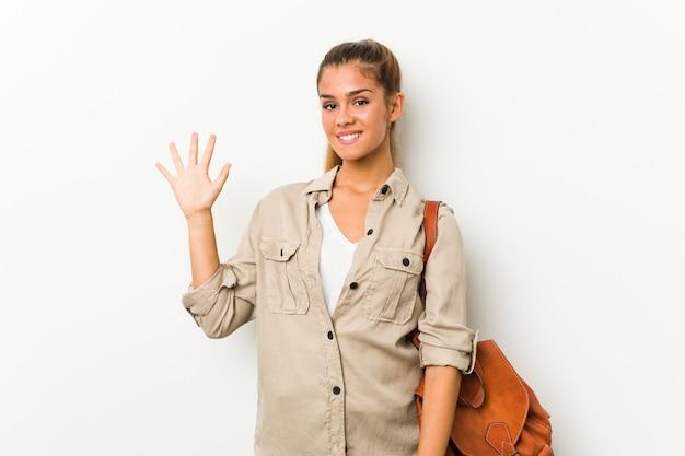 Giovane donna caucasica pronta per un viaggio che mostra allegro mostrando il numero cinque con le dita.