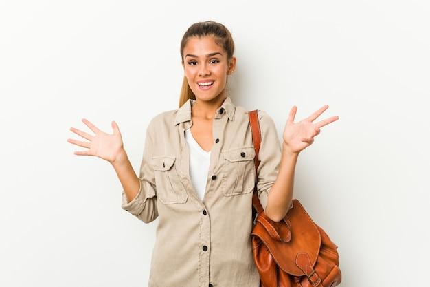 Giovane donna caucasica pronta per un viaggio che riceve una piacevole sorpresa, eccitata e alzando le mani.