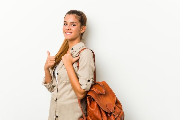 Giovane donna caucasica pronta per un viaggio che sorride e che alza pollice in su