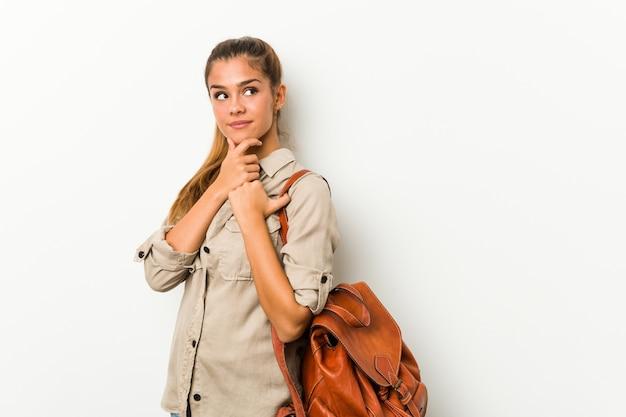 Giovane donna caucasica pronta per un viaggio guardando lateralmente con espressione dubbiosa e scettica.