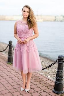 Giovane donna caucasica riccia in abito rosa rosa sotto le ginocchia sull'argine.