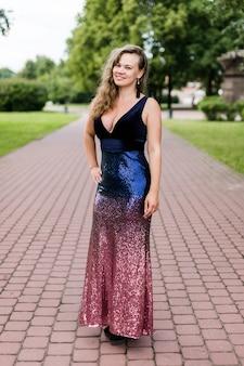 Giovane donna caucasica riccia sorridente in vestito lungo il pavimento con la scollatura bassa in parco.