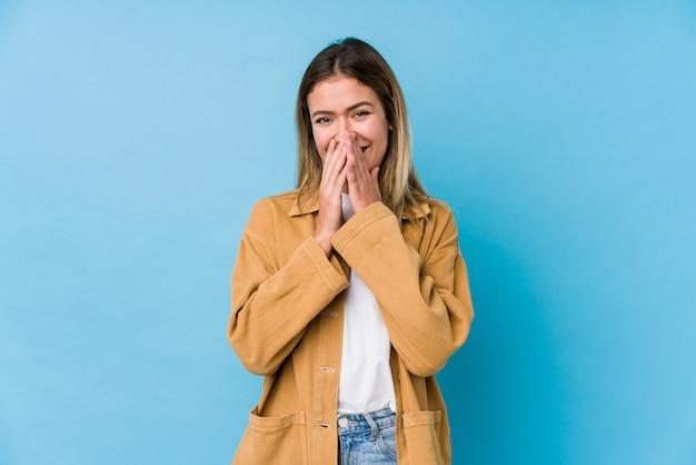 Giovane donna caucasica ridendo di qualcosa, coprendo la bocca con le mani.