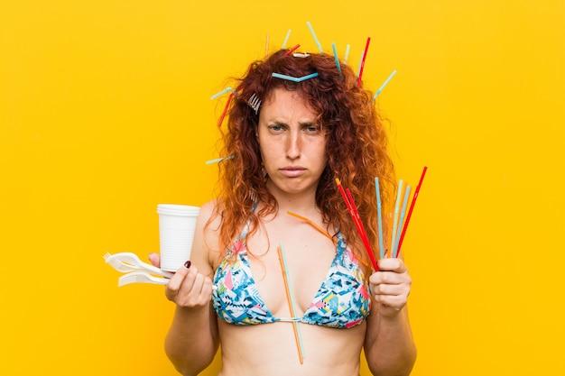 Giovane donna caucasica rossa arrabbiata con l'uso abusivo di plastica