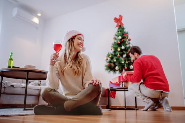 Giovane donna caucasica sorridente attraente con il cappello di santa sulla testa che si siede sul pavimento e che beve vino. sullo sfondo il suo ragazzo mette regali sotto l'albero. concetto di vacanze di natale.