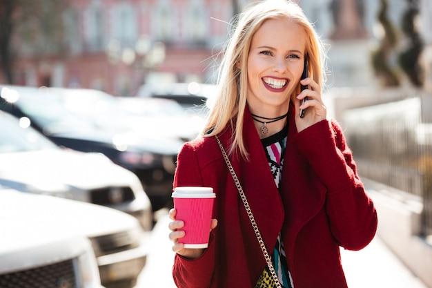 Giovane donna caucasica sorridente che cammina all'aperto che parla dal telefono