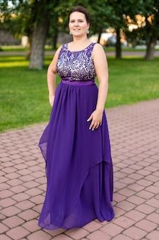 Giovane donna caucasica sorridente del brunette in vestito viola fino al pavimento con ricamo in sosta.