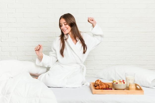 Giovane donna caucasica sul letto ballare e divertirsi.