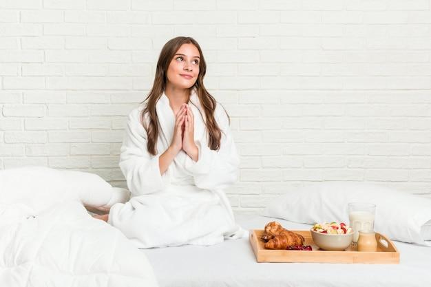 Giovane donna caucasica sul letto che compongono il piano in mente, creando un'idea.
