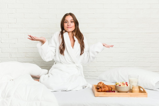 Giovane donna caucasica sul letto che dubita e che scrolla le spalle le spalle nel gesto interrogante.