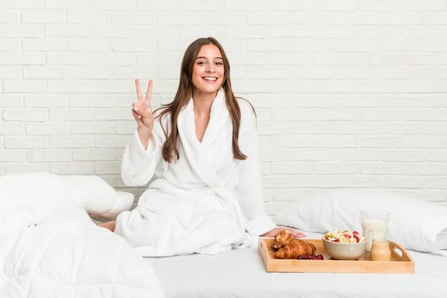 Giovane donna caucasica sul letto che mostra il segno di vittoria e che sorride ampiamente.