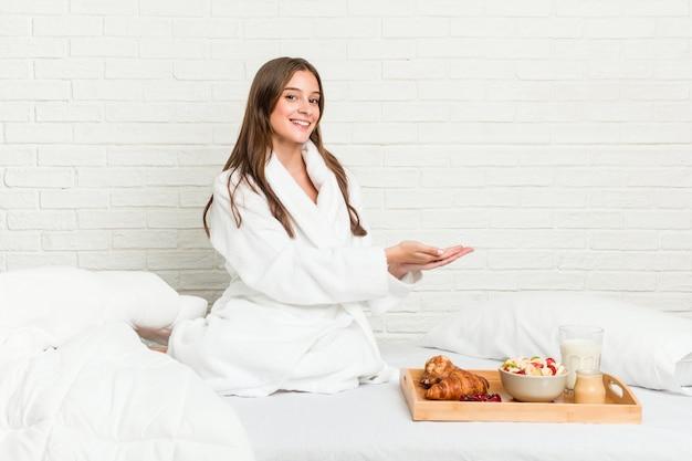 Giovane donna caucasica sul letto in possesso di una copia su una palma.