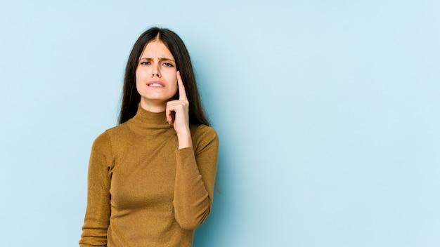 Giovane donna caucasica sul muro blu piangendo, insoddisfatto di qualcosa