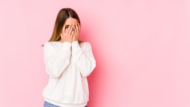 Giovane donna caucasica sul muro rosa lampeggia verso la telecamera attraverso le dita, imbarazzato volto che copre.
