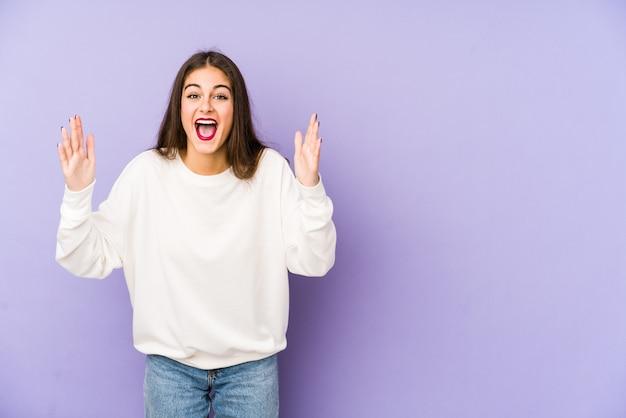 Giovane donna caucasica sul muro viola che riceve una piacevole sorpresa, eccitato e alzando le mani.